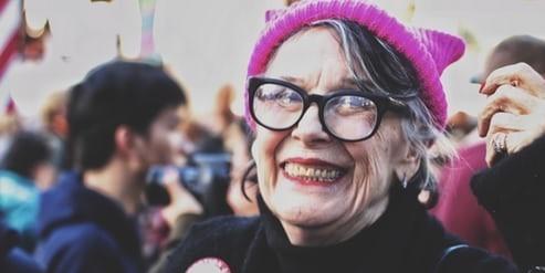 Altere Damen auf dem Women's Marche mit einer Kitty-Mütze, sie lacht in die Kamera