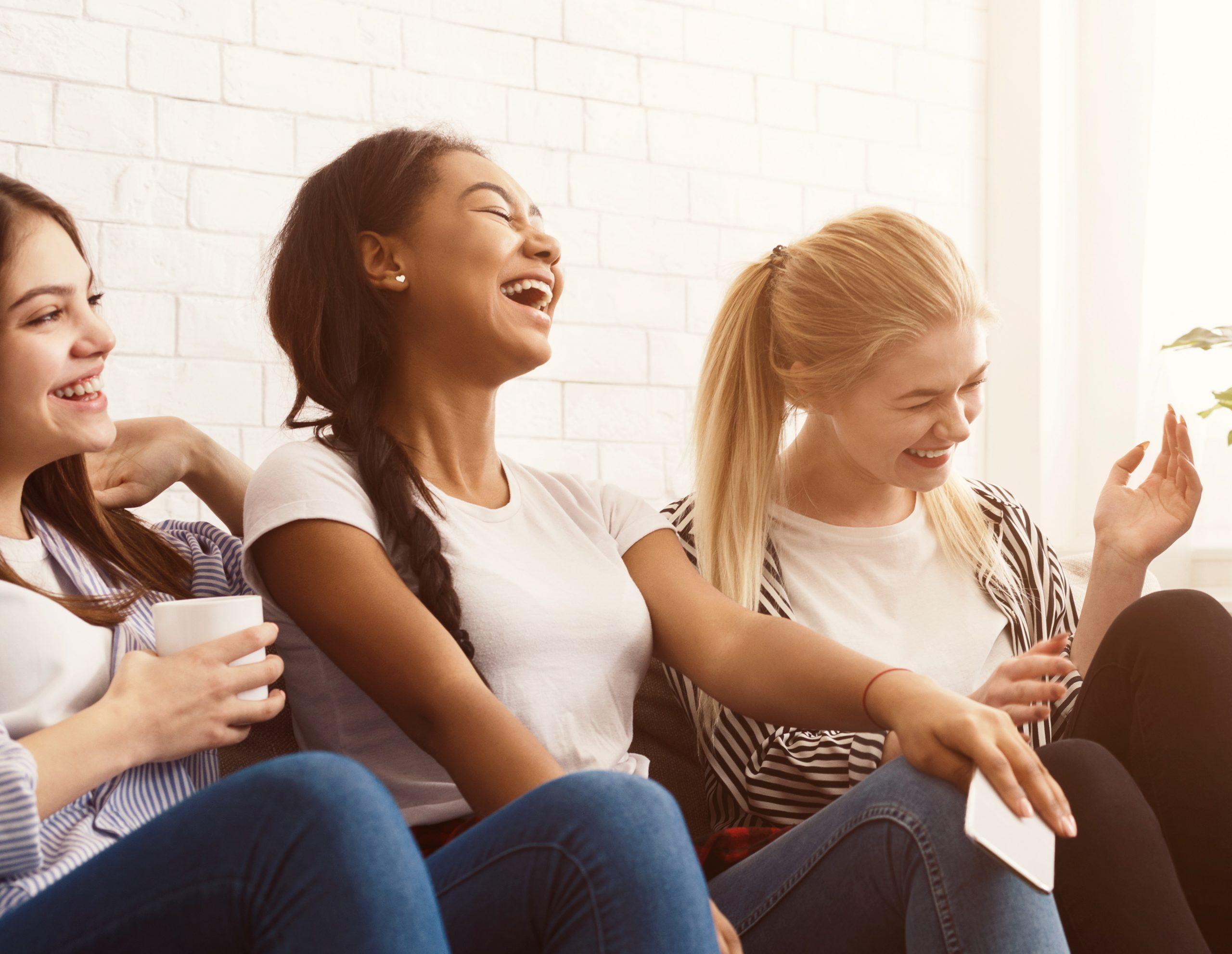 Drei lachende junge Frauen, die sich im Rahmen eines Worldcafés unterhalten